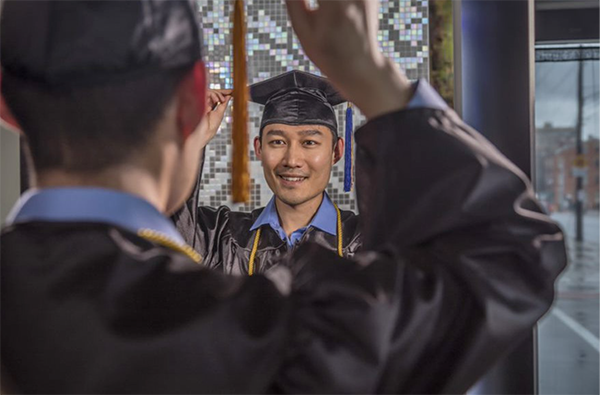 student putting on graduation cap in mirror